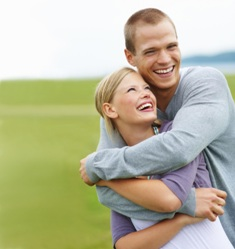 Portrait of a happy couple embracing eachother against a green field