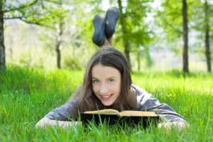 Young student reading book in park